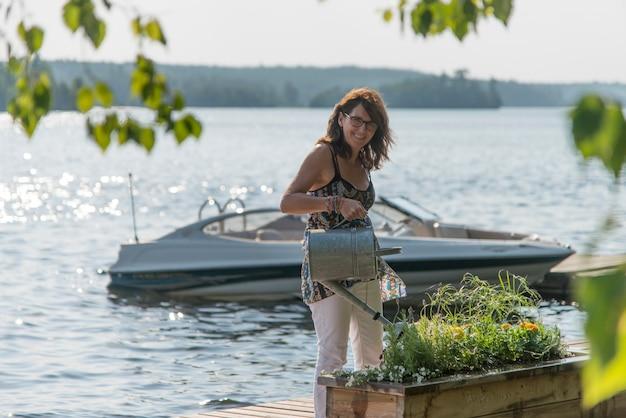 Bewässerungsanlagen der frau auf einem dock, see des holzes, ontario, kanada Premium Fotos