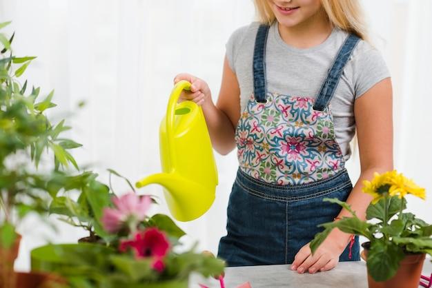 Bewässerungsblumen des jungen mädchens der nahaufnahme Kostenlose Fotos