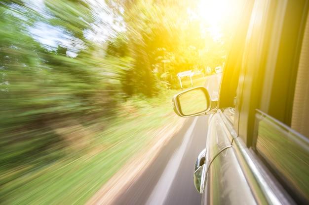 Bewegliches auto auf der straße zwischen wald Premium Fotos