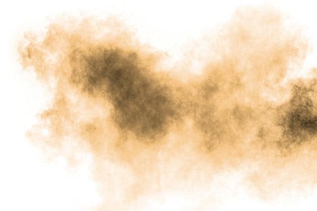 Bewegung der braunen staubexplosion einfrieren. bewegung des braunen pulvers stoppen. explosives braunes pulver auf weißem hintergrund. Premium Fotos