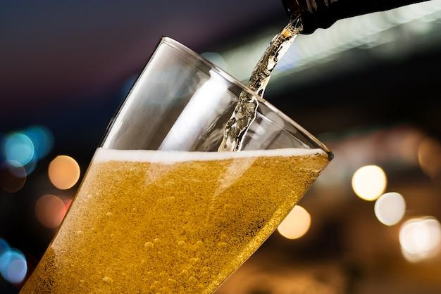 Bewegung des bieres gießend aus flasche in glas Premium Fotos