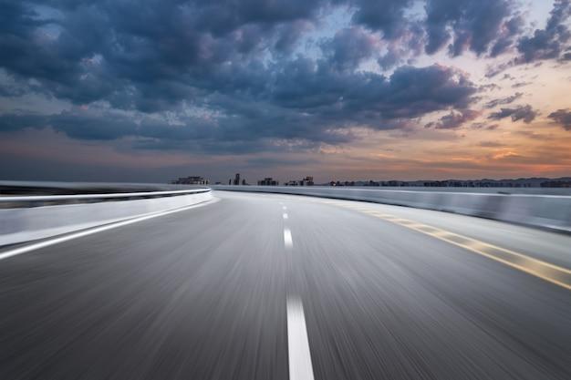 Bewegung-unscharfe landstraße in den dämmerungswolken Premium Fotos