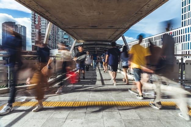 Bewegungsunschärfe von den gedrängten asiatischen leuten, die auf erhöhten öffentlichen gehweg gehen Premium Fotos