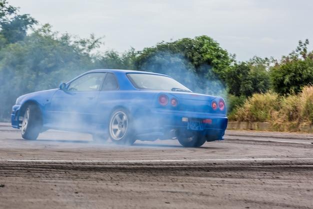 Bewegungsunschärfeautreiben, treibendes auto des berufsfahrers auf rennstrecke mit dem rauchen. Premium Fotos