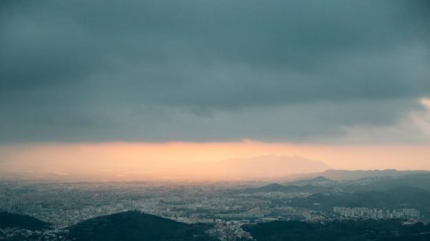 Bewölkte wolken über dem berg und dem stadtbild Kostenlose Fotos