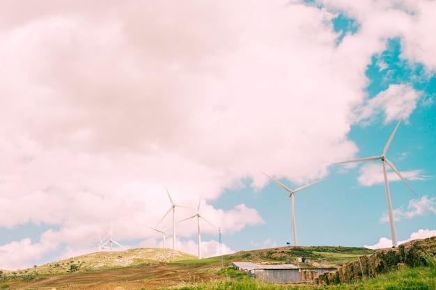 Bewölkter himmel über ländlichem mit windmühlen Kostenlose Fotos