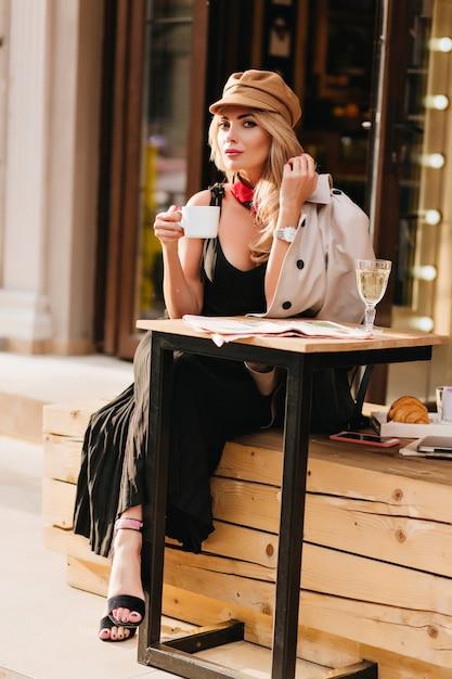Bezaubernde blonde frau in der braunen weinlesekappe, die heißen kaffee am kalten tag genießt. außenporträt des freudigen stilvollen mädchens in den eleganten schwarzen sandalen, die zeit im café verbringen und tee trinken. Kostenlose Fotos