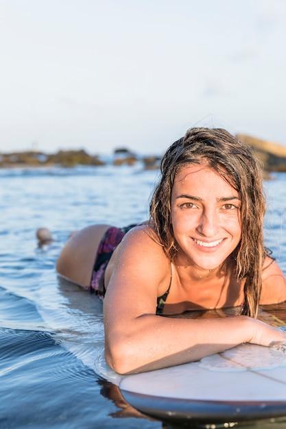 Bezaubernde dame, die auf surfbrett liegt Kostenlose Fotos