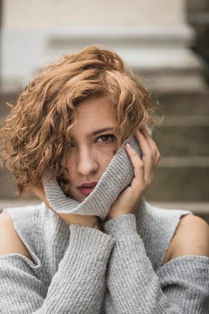 Bezaubernde dame mit kurzem lockigem haar, das den kragen der strickjacke hält Kostenlose Fotos