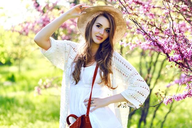 Bezaubernde hübsche junge frau mit langen haaren im sommerhut, weißes helles kleid, das im sonnigen garten auf blühendem sakura-hintergrund geht. entspannung, lächeln in die kamera, leichte kleidung, sensibilität, freude Kostenlose Fotos
