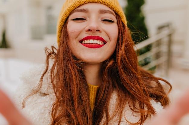Bezaubernde langhaarige frau im hut, die mit geschlossenen augen lacht. foto im freien des begeisterten ingwermädchens, das glück im winter ausdrückt. Kostenlose Fotos