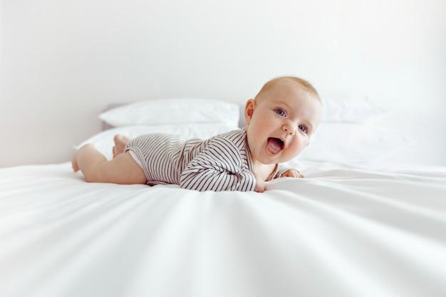 Bezauberndes glückliches baby auf weißem bett Premium Fotos