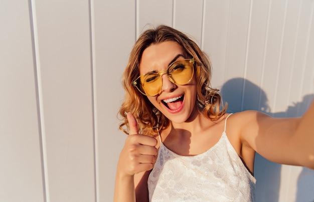 Bezauberndes lächelndes mädchen in den gelben brillen, die oben einen daumen blinzeln und zeigen Kostenlose Fotos