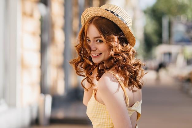 Bezauberndes mädchen mit dunklem lockigem haar, das an warmen sommertagen im freien herumalbert. erstaunliches weibliches modell des ingwers im hut und im gelben kleid, die auf städtischer straße lachen. Kostenlose Fotos