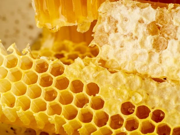 Bienenbienenwabennahaufnahme, frischer fadenziehender süßer honig, makro Premium Fotos