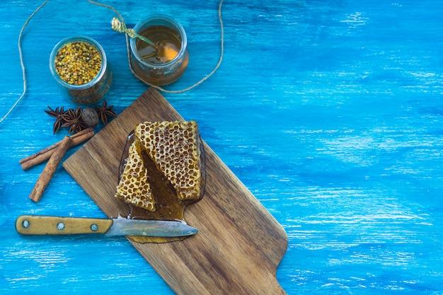 Bienenpollen glas; gewürze und bienenwabenstück mit messer gegen blauen strukturierten hintergrund Kostenlose Fotos