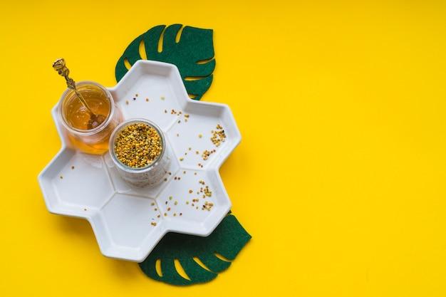 Bienenpollen und -honig im weißen behälter auf gelbem hintergrund Kostenlose Fotos