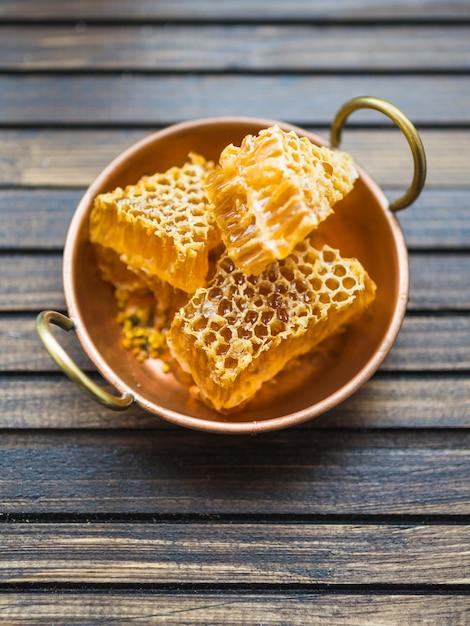 Bienenwabenstücke im kupfernen gerät mit griffen auf holztisch Kostenlose Fotos