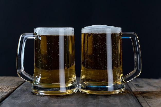 Bier im glas auf dem holztisch und dem schwarzen hintergrund Premium Fotos