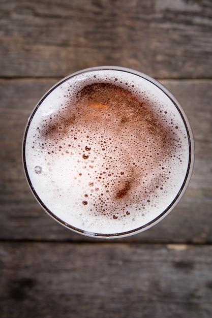 Bier im glas. bier schaum. ansicht von oben genanntem auf dunklem holztisch Premium Fotos