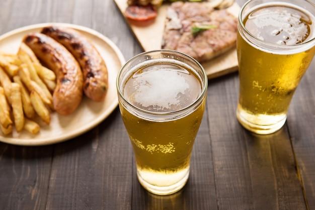 Bier im glas mit gourmetsteak und pommes frites auf hölzernem hintergrund Premium Fotos