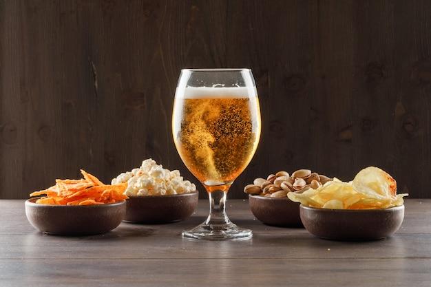 Bier in einem becherglas mit junk-food-seitenansicht auf einem holztisch Kostenlose Fotos