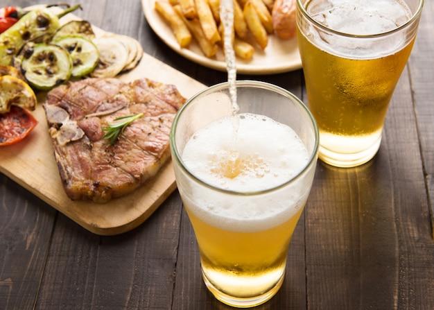 Bier wird in glas mit gourmet-steak und pommes frites auf hölzernem hintergrund gegossen Premium Fotos