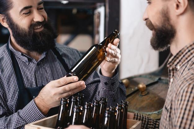 Bierbrauer testet flaschen auf bierfüllenden liebesjob. Premium Fotos