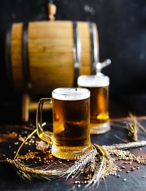 Biergläser und weizengewürz auf einer alten rustikalen hölzernen tabelle auf schwarzem hintergrund Premium Fotos