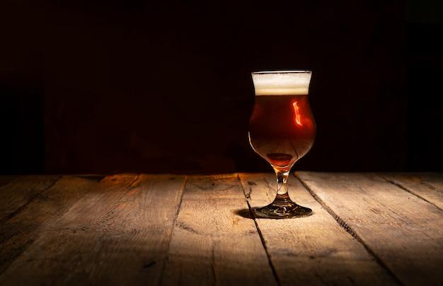Bierglas auf einem dunklen hölzernen hintergrund mit kopienraum Premium Fotos
