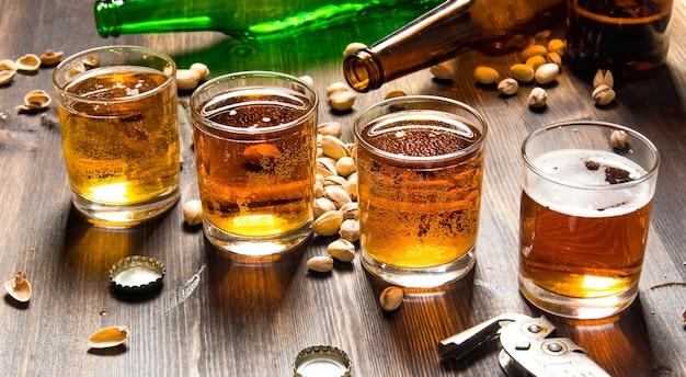 Bierhintergrund. vier biere mit pistazien auf einem holztisch. Premium Fotos