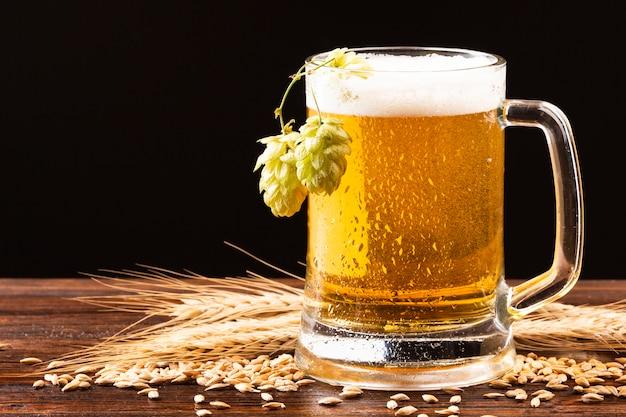 Bierkrug mit hopfen auf hölzernem brett Premium Fotos