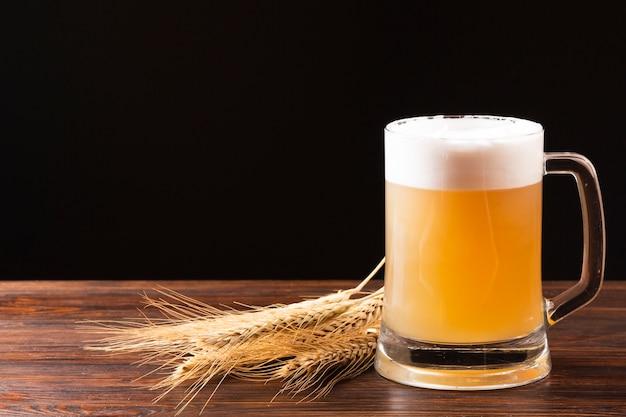 Bierkrug und gerste auf holzbrett Kostenlose Fotos