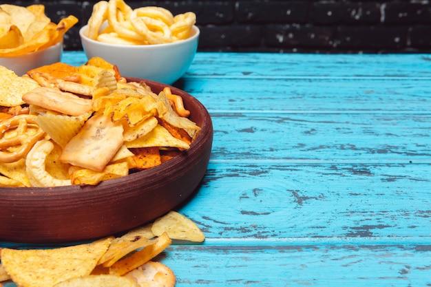 Biersnacks wie cracker, chips, kekse auf einer holzoberfläche Premium Fotos