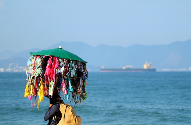 Bikini-verkäufer, der viele bikinis geht auf copacabana-strand, rio de janeiro, brasilien trägt Premium Fotos