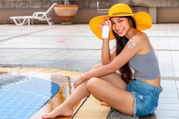 Bikinihutfrau, die befeuchtende lichtschutzlotion auf schulter aufträgt. Premium Fotos