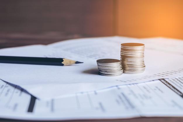 Bilanz mit bleistift und münzen auf kontoauszug, kontokonzept. Premium Fotos