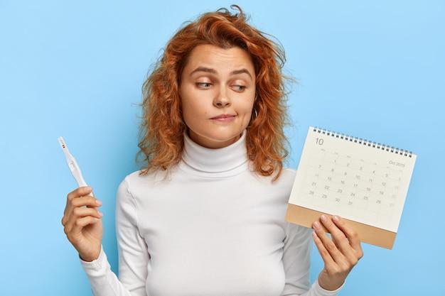 Bild der attraktiven frau hält schwangerschaftstest und periodenkalender Kostenlose Fotos