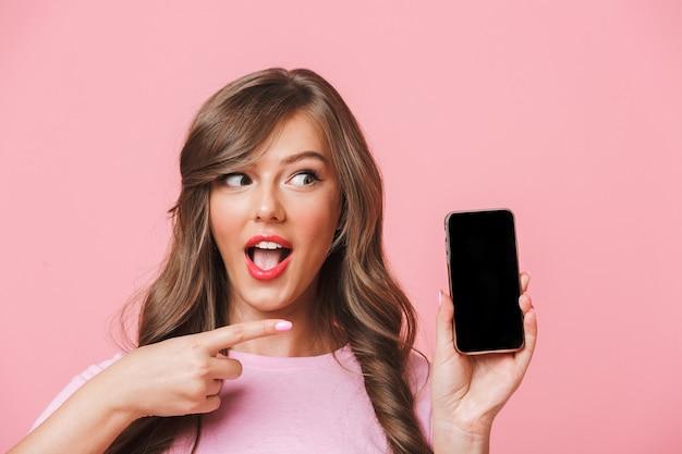 Bild der europäischen frau, die schöne braune schlösser hält, die handy in händen halten und finger auf schwarzen bildschirm des copyspace zeigen, lokalisiert über rosa hintergrund Premium Fotos