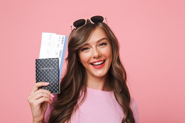 Bild der europäischen frau, die schöne braune schlösser lächelt, während sie pass und flugtickets hält, lokalisiert über rosa hintergrund Premium Fotos