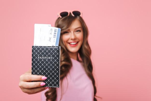 Bild der freudigen schönen frau in der freizeitkleidung, die pass und flugtickets an der kamera zeigt, lokalisiert über rosa hintergrund Premium Fotos