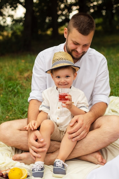 Bild der fröhlichen jungen kaukasischen frau und des mannes hält ihr kind auf händen, lächelt und freut sich Premium Fotos