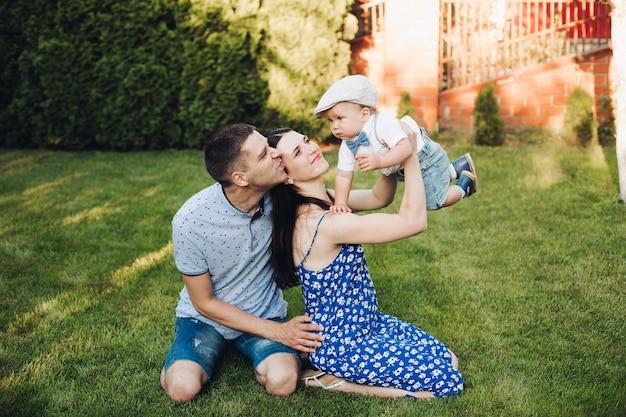 Bild der fröhlichen kaukasischen mutter, des vaters und ihres kindes haben spaß zusammen und lächelt im garten Premium Fotos