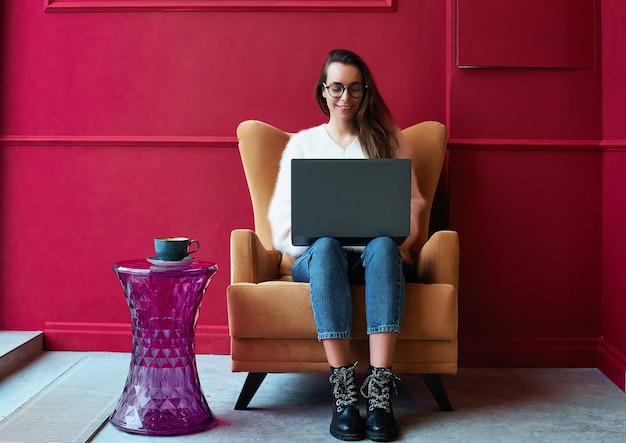 Bild der glücklichen frau, die laptop beim sitzen am café verwendet. merican frau, die in einer kaffeestube sitzt und an laptop arbeitet. Premium Fotos