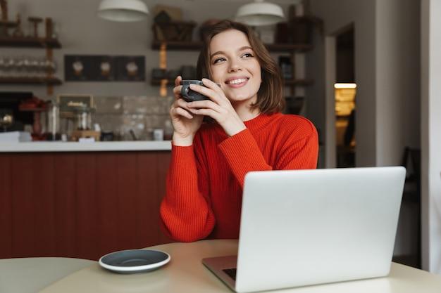 Bild der glücklichen kaukasischen frau 20s lächelnd, während laptop und kaffee im café trinkend Premium Fotos
