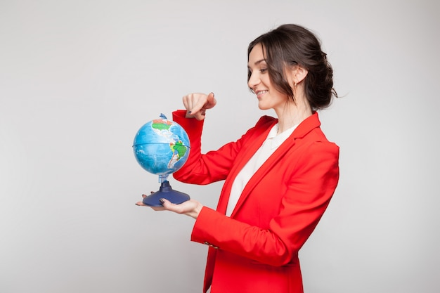 Bild der hübschen frau im roten blazer mit erdkugel in den händen Premium Fotos