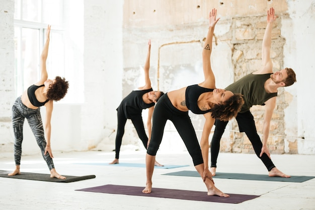 Bild der jungen leute, die yoga im fitnessstudio tun Kostenlose Fotos