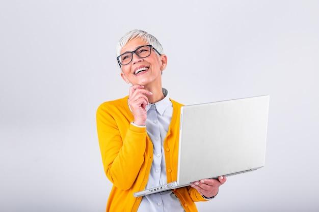 Bild der netten reifen frauenstellung lokalisiert über grauem hintergrund unter verwendung der laptop-computers. porträt einer lächelnden älteren dame, die laptop-computer hält Premium Fotos