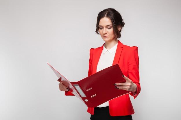Bild der schönheit im roten blazer, der mit dokumenten in den händen steht Premium Fotos