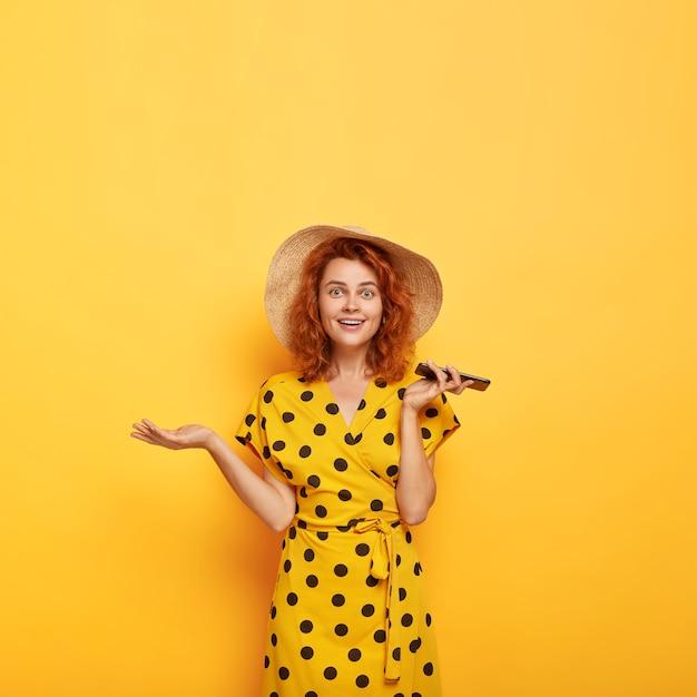 Bild der verwirrten überraschten schönen rothaarigen dame hebt handfläche, hält handy, freut sich über neukauf, trägt strohhut und gepunktetes gelbes kleid. weiblichkeit, lebensstil Kostenlose Fotos